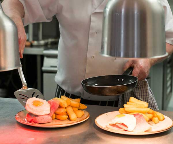 Chef serving eggs, gammon and chips at Timothy's restaurant