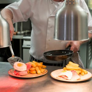 Chef serving lunch on counter out of pan with ham, egg, and chips